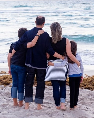 This image has an empty alt attribute; its file name is family-on-beach.jpg
